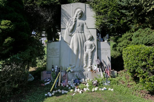 "Items left by visitors decorate the grave of George Herman ""Babe"" Ruth and Claire Ruth at the Gates of Heaven Cemetery in Hawthorne, N.Y., Wednesday, Aug. 15, 2018. Seventy years after Babe Ruth's death, fans still flock to his grave with tributes: baseballs, bats, beer and more. The indelible slugger and larger-than-life personality died Aug. 16, 1948."