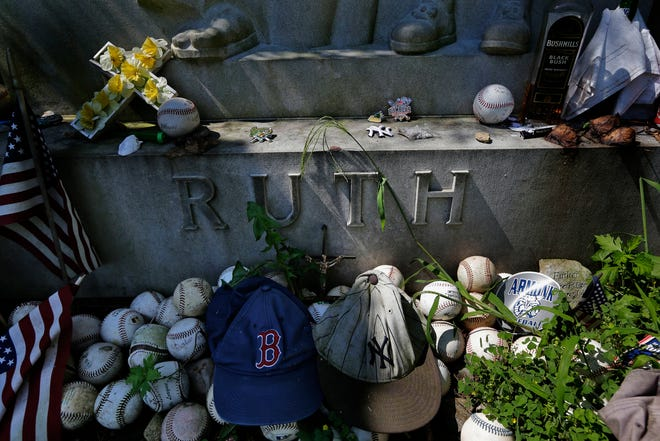 """Items left by visitors decorate the grave of George Herman """"Babe"""" Ruth and Claire Ruth at the Gates of Heaven Cemetery in Hawthorne, N.Y., Wednesday, Aug. 15, 2018.  Seventy years after Babe Ruth's death, fans still flock to his grave with tributes: baseballs, bats, beer and more. The indelible slugger and larger-than-life personality died Aug. 16, 1948."""