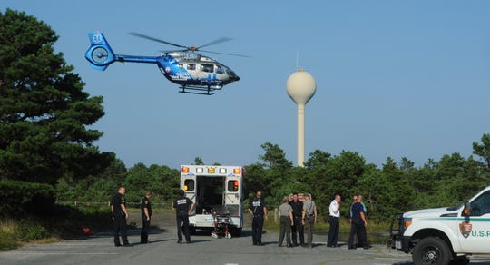 A MedFlight helicopter takes off from behind Cape Cod National Seashore headquarters with a man who was attacked by a shark, Wednesday, Aug. 15, 2018 in South Wellfleet, Mass. A man swimming off Cape Cod was attacked by a shark on Wednesday and was airlifted to a hospital. It was the first shark attack on a human on the popular summer tourist destination since 2012.