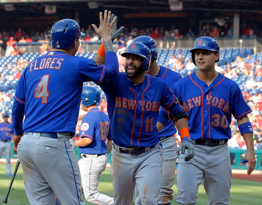 New York Mets' Jose Bautista, center, high-fives Wilmer Flores after Bautista hit a grand slam during the fifth inning of a baseball game against the Philadelphia Phillies, Thursday, Aug. 16, 2018, in Philadelphia.