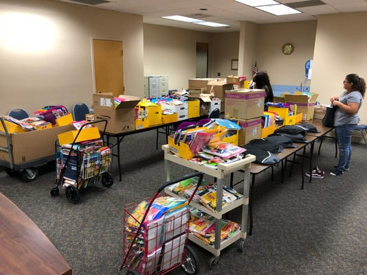 Local volunteers work on filling backpacks with school supplies.