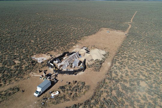 In this Friday, Aug. 10, 2018 file photo aerial view of a makeshift compound is seen in the desert area of Amalia, N.M. New Mexico forensic investigators announced Thursday, Aug. 16, that a highly decomposed body found at a desert compound in New Mexico has been identified as a missing Georgia boy whose father is accused of kidnapping him and performing purification rituals on the severely disabled child. The New Mexico Office of the Medical Investigator said Thursday that the remains were those of Abdul-ghani Wahhaj.