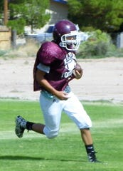 A member of the Tularosa High School Football Team catches a football during drills at a practice Wednesday.