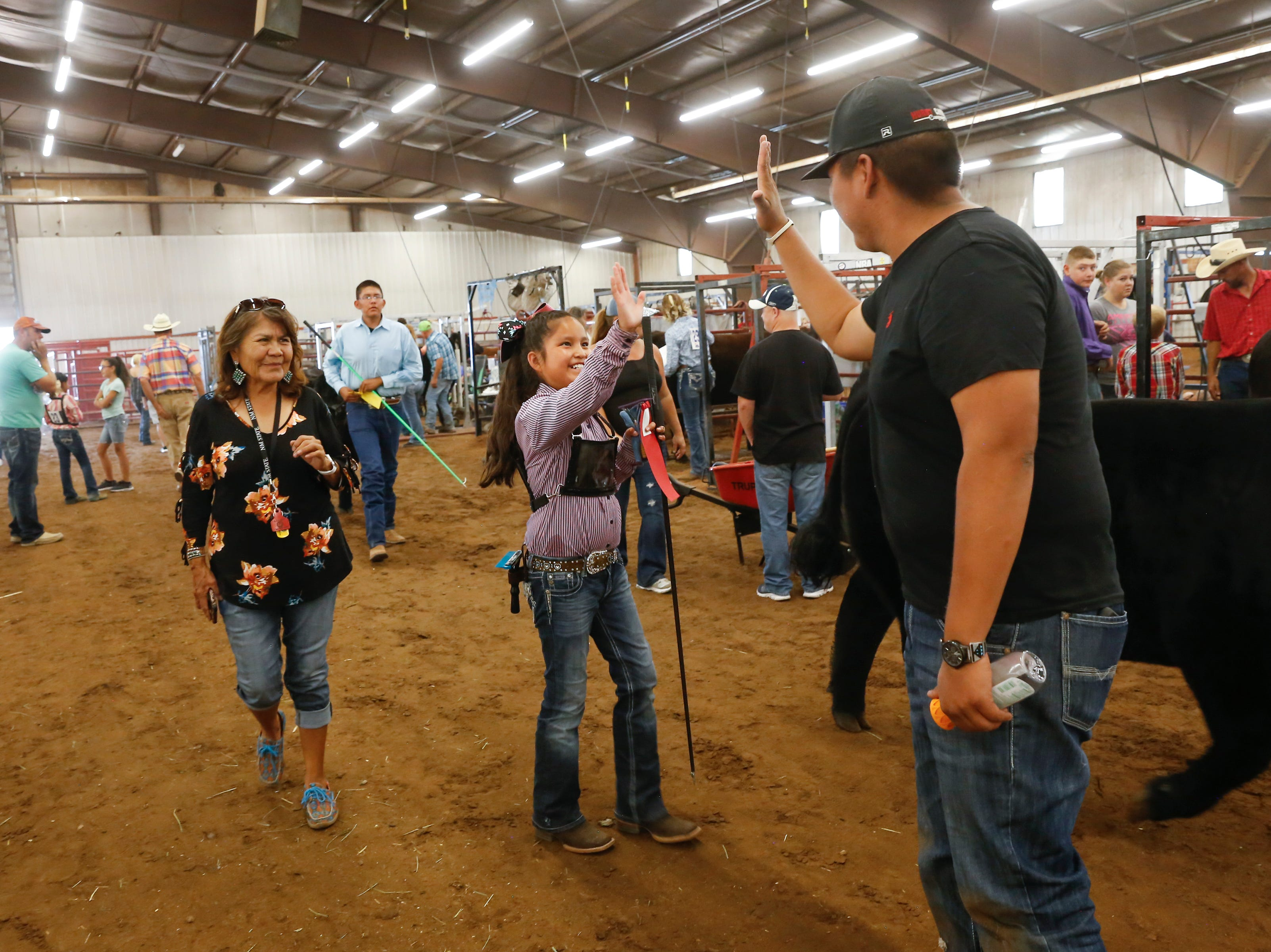 Tatum Lantana, center, gets a high five from Matt Denetclaw, right, after Lantana scored second place with her steer Major, Thursday, Aug. 16, 2018 at the annual beef show at the San Juan County Fair at McGee Park in Farmington.