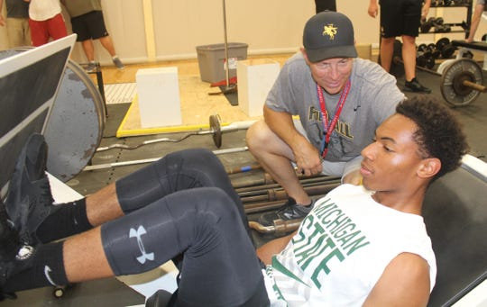 North Farmington's second-year head coach Bob Chiesa oversees a weight-room workout by Raiders sophomore Andre Ballard.