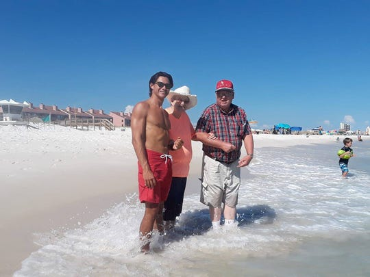Pensacola Beach lifeguard Alex Hernandez helps an elderly couple reach the Gulf waters.