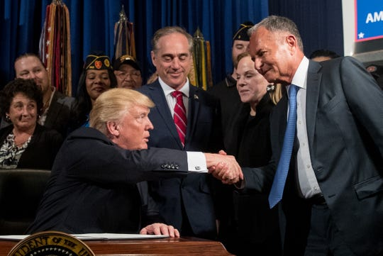 """President Donald Trump, left, accompanied by Veterans Affairs Secretary David Shulkin, center, shakes hands with Isaac """"Ike"""" Perlmutter, an Israeli-American billionaire, and the CEO of Marvel, right, before signing an Executive Order on """"Improving Accountability and Whistleblower Protection"""" at the Department of Veterans Affairs, Thursday, April 27, 2017, in Washington. Also pictured is Laura Perlmutter, second from right. (AP Photo/Andrew Harnik)"""