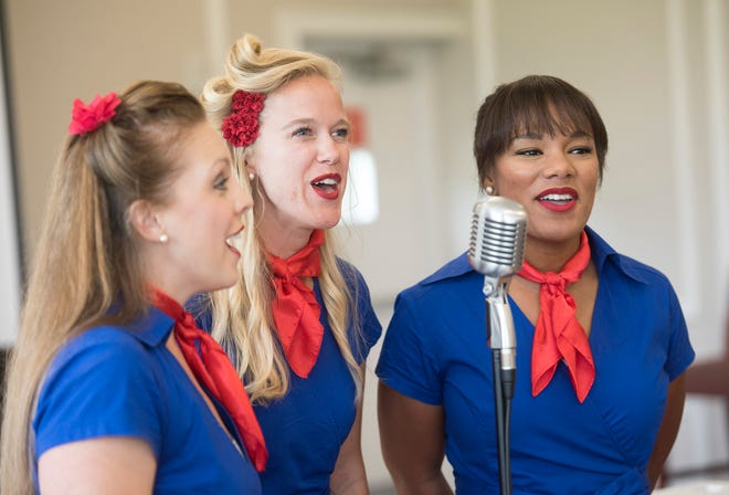 Amie Glazier, Goldie Lahr and Veancha White, who are part of the singing group the Blue Anchor Belles, entertain the crowd at the Military Spouse Entrepreneurship Symposium Thursday at Pensacola Naval Air Station.