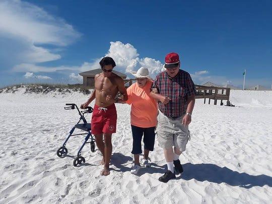 Pensacola Beach lifeguard Alex Hernandez helps an elderly couple reach the Gulf waters.