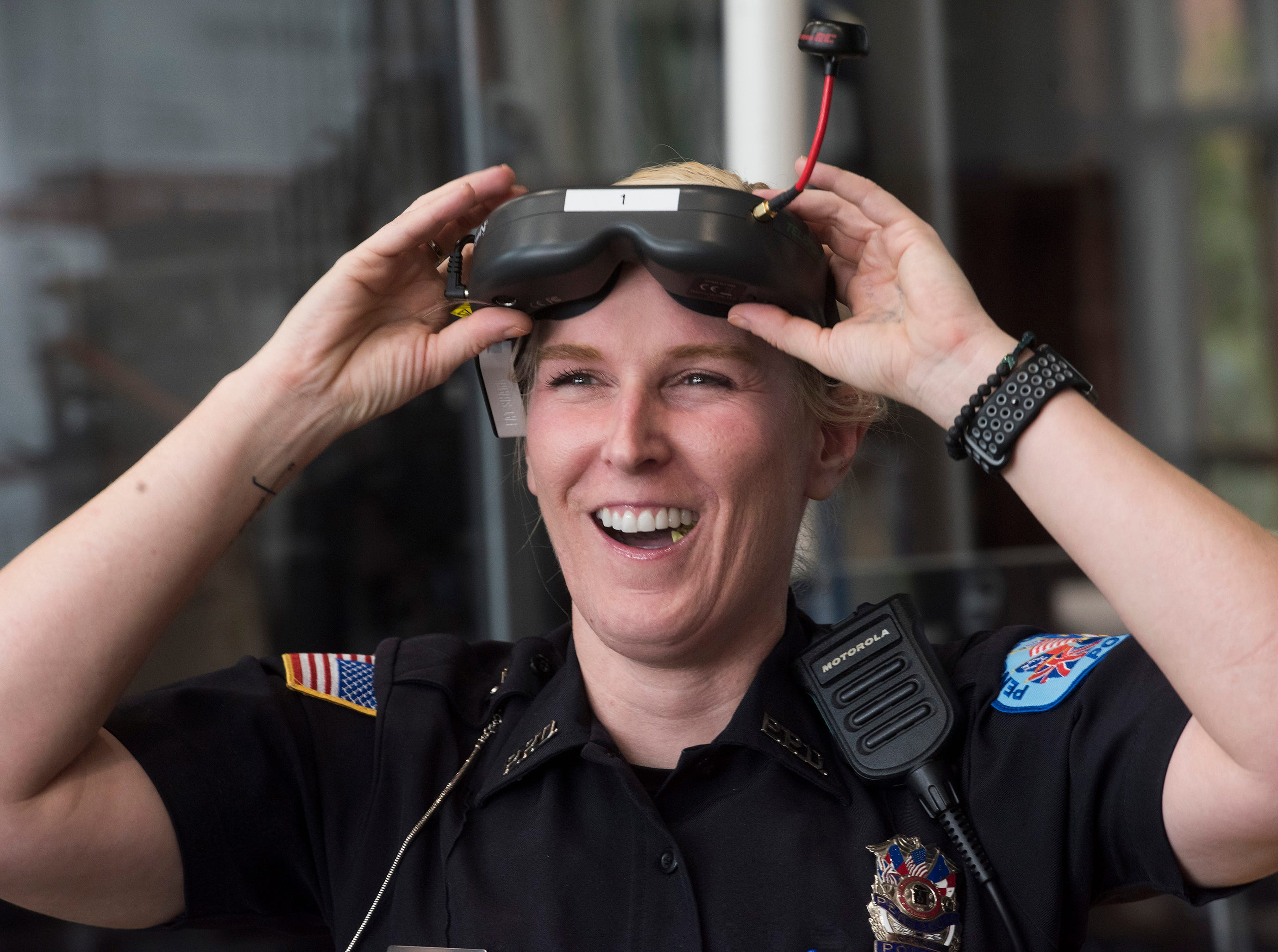 Pensacola Police Department Officer Kelly Eierhart reacts to seeing a flight demonstration from a drone at the Institute of Human and Machine Cognition on Thursday, Aug. 16, 2018.