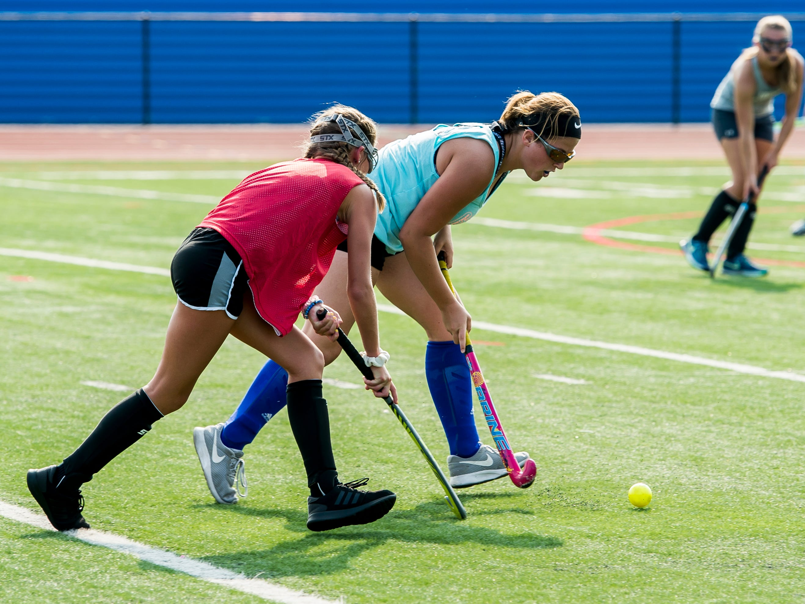 Spring Grove field hockey players Kaylee Grubb, left, and Grace Slenker chase after the ball during practice on Wednesday, August 15, 2018.