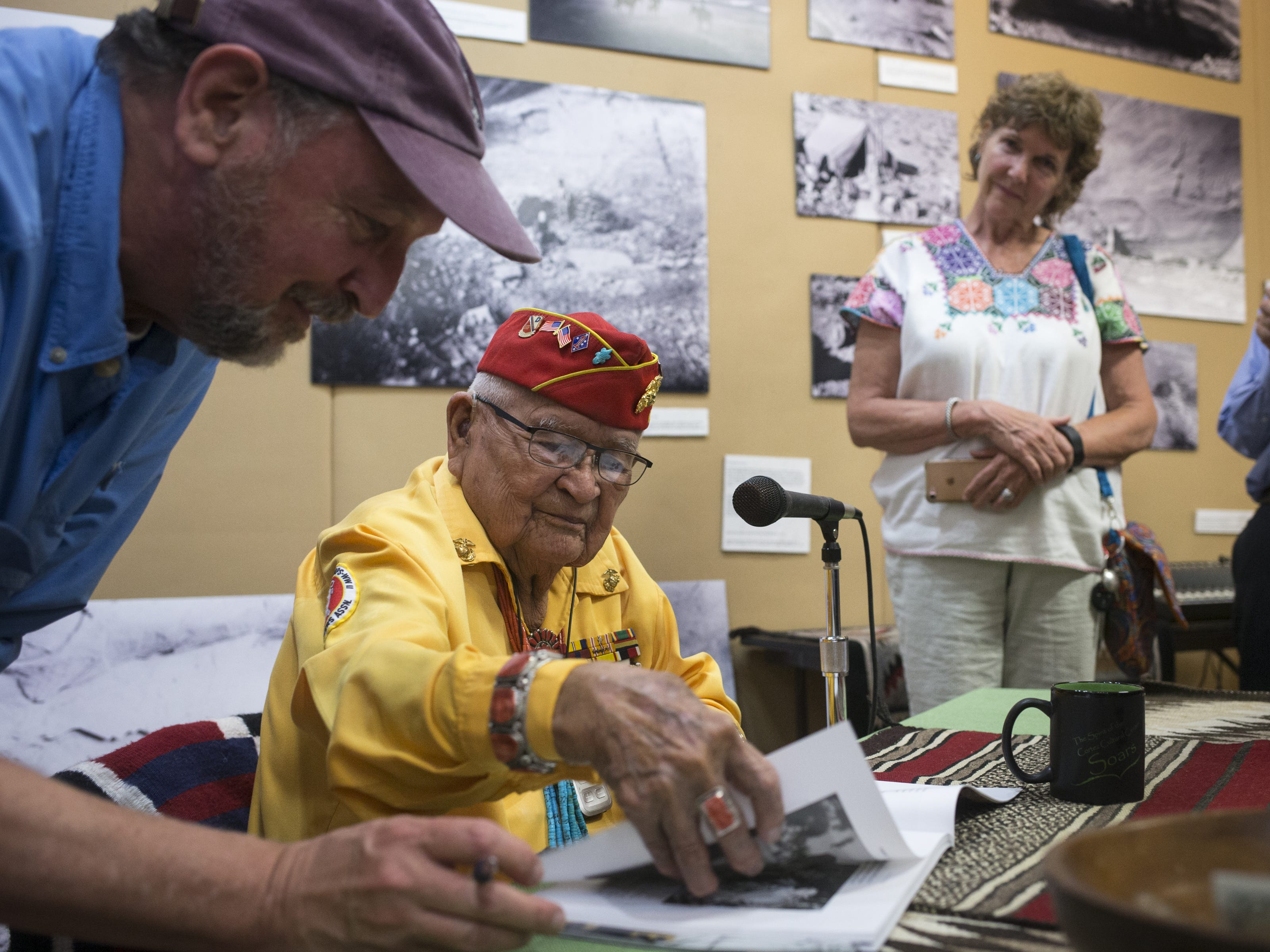 Navajo Code Talker Sam Sandoval signs a book on Aug. 14, 2018, after speaking at the Cortez Cultural Center in Cortez, Colorado.