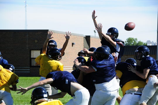 Capac High School football players practice kicking and blocking extra points.