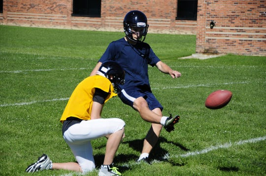 Ben Laskowski kicks a point after during a Capac High School football practice.