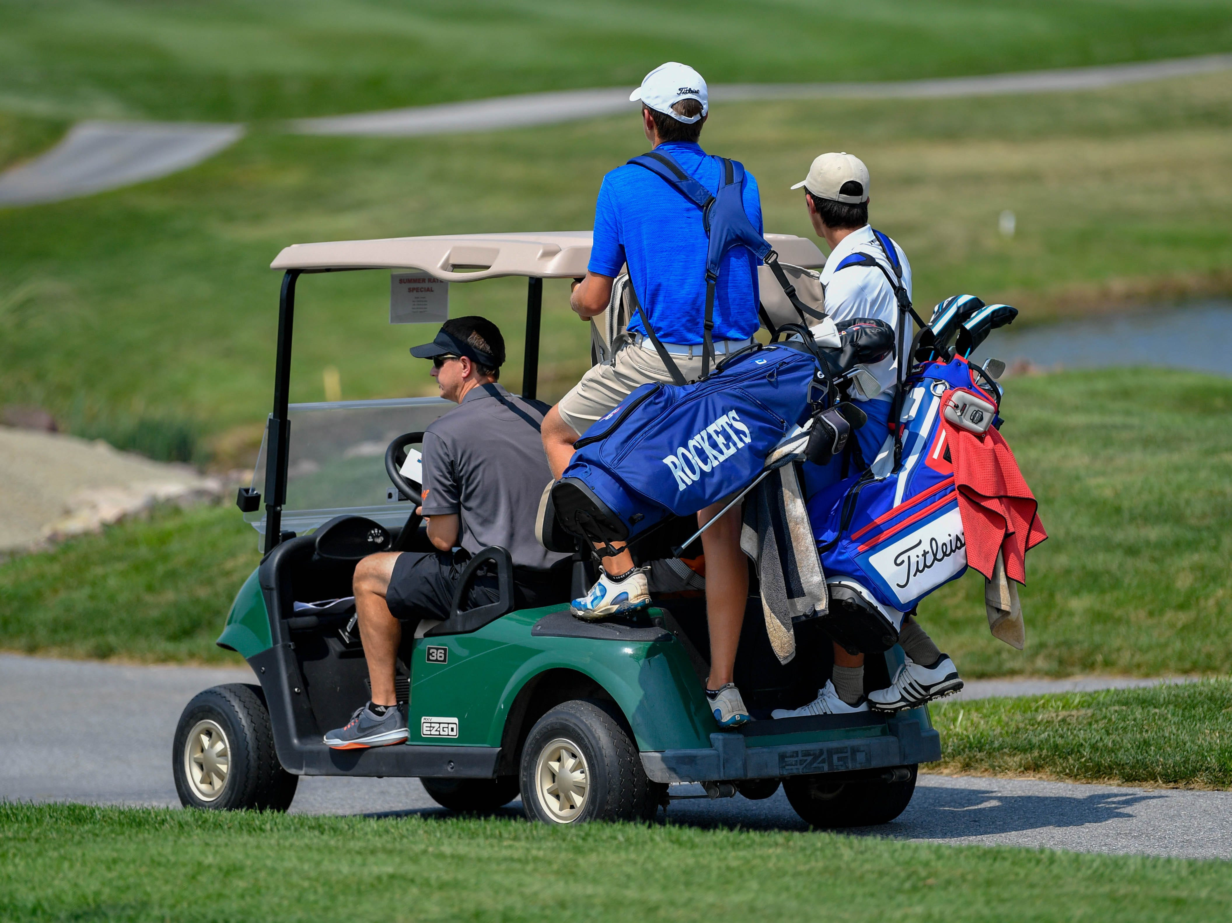 Spring Grove and Dallastown golfers hitch a ride with Northeastern's coach to the next hole during a Division I golf match at Royal Manchester Golf Links, Wednesday, Aug. 16, 2018.