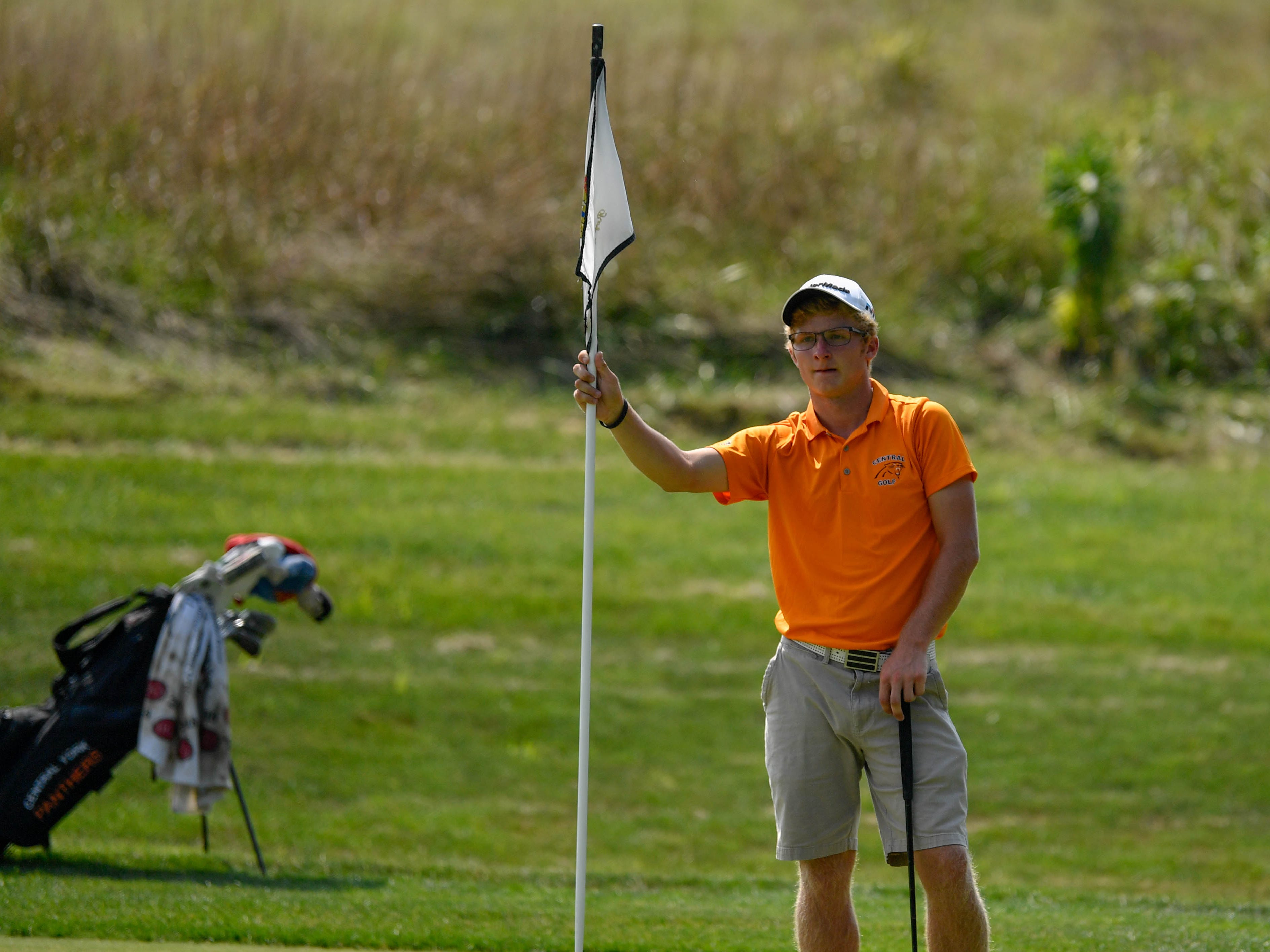 Central York's Carson Bacha tends the flag for an opponent during a division I golf match at Royal Manchester Golf Links, Wednesday, Aug. 16, 2018.