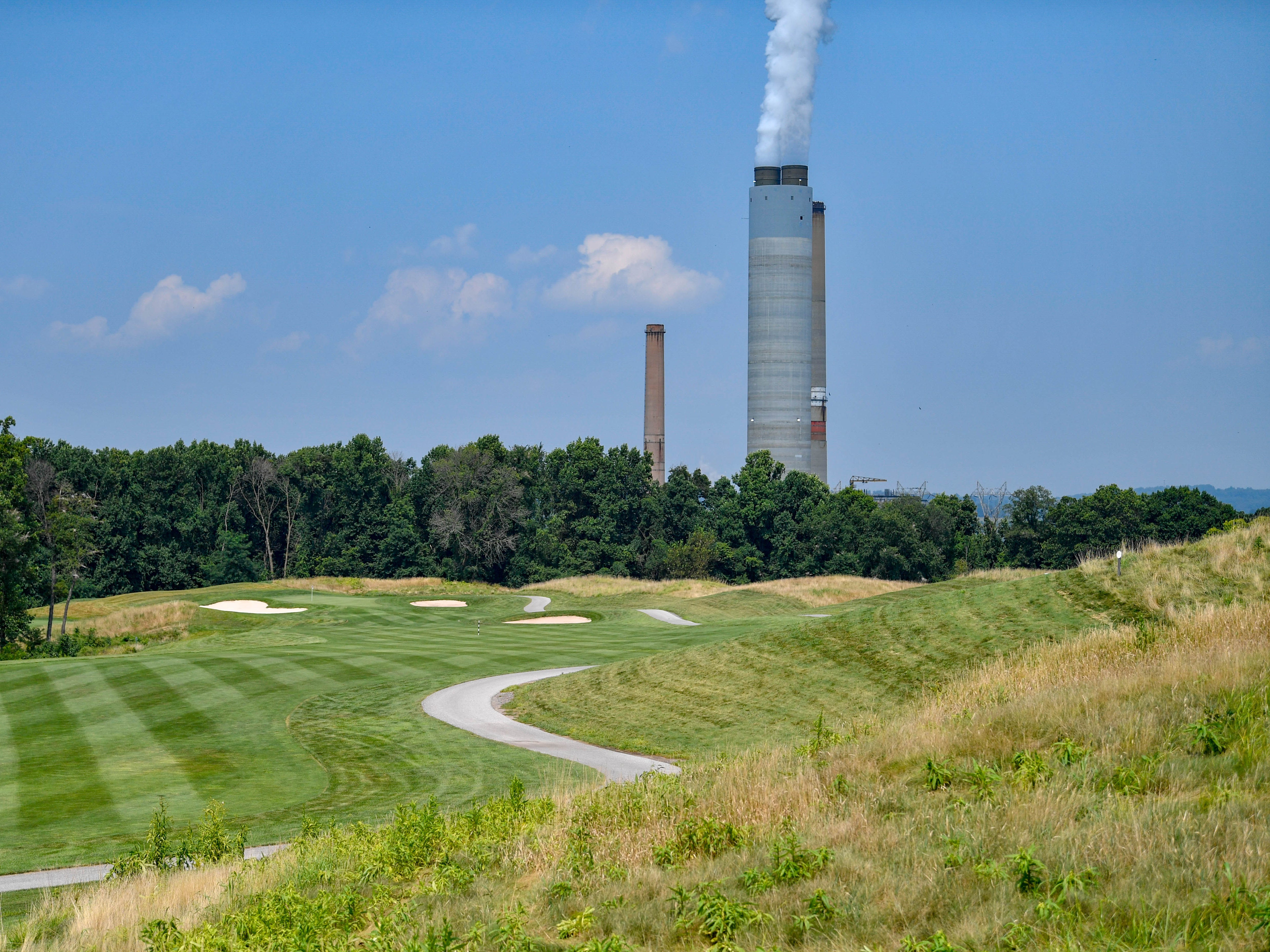 Smokestack backdrops make for unique views for competitors at Royal Manchester Golf Links, Wednesday, Aug. 16, 2018.