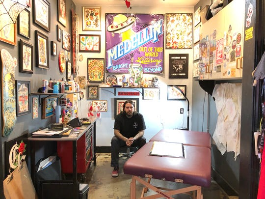 """Reno tattoo artist Tony Medellin poses in his booth at Lasting Dose tattoo shop in Midtown. His walls are covered in other artists' works. On the right, some of his own line drawings stick to a board. Medellin will be in season 11 of """"Ink Masters"""" reality TV show starting Aug. 28, 2018."""
