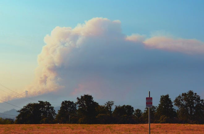 A large cloud of smoke can be seen Wednesday evening in north Redding in the direction of the Carr and Hirz fires.