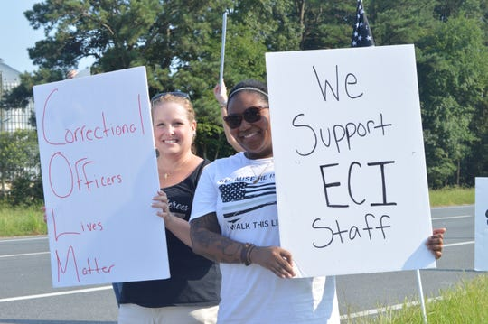 Bobbie Wigglesworth (left) and Kerry Carr, organizers of the Support ECI group, stand with signs at the intersection of Route 13 and Revells Neck Road during a rally on Aug. 15, 2018.