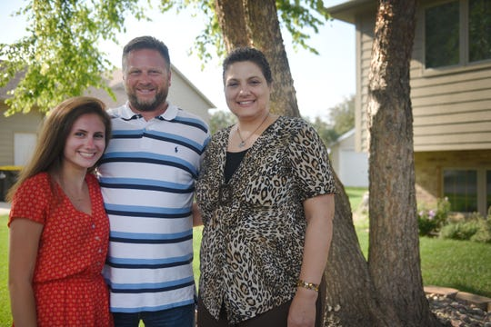 Olivia Warne and her parents Charles and Maria stand Wednesday, July 25,  outside of their home in Sioux Falls.