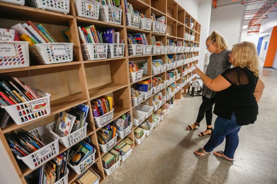 Teachers Angie Collins, right, and Sarah Pulliam organize the large bookcase at the Summit Preparatory School on Wednesday, Aug. 16, 2018.