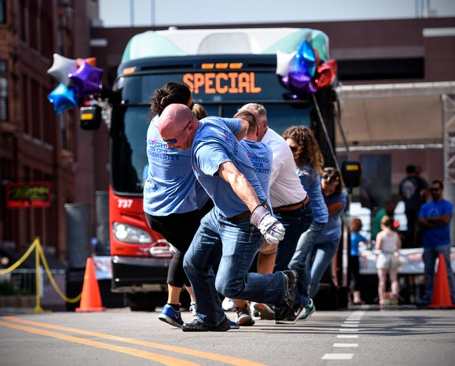 Falcon National Bank team members join forces to pull a 15-ton bus during the New Flyer Annual United Way Community Bus Pull Thursday, Aug. 16, on Fifth Avenue in Downtown St. Cloud.