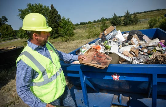 General Manager Jon Snyder shows an example of a cardboard pizza box that is contaminated with grease and not able to be recycled Wednesday, Aug. 15, at the Republic Services Transfer Center in East St. Cloud.
