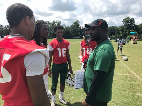 Head coach Willie Simmons discusses the offense with the quarterbacks. From left to right: D.J. Phillips, Rasean McKay, Isaac Sullivan and Ryan Stanley (starter).