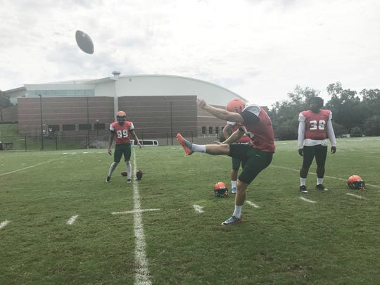 Punter Chris Faddoul sends the ball off deep during practice.