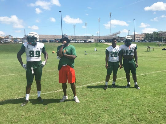 Tight ends coach James Spady looks on with his players. From left to right: Anthony Jones (89), Kevin Newman (26) and Taymel Christian (47).