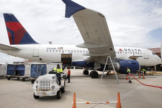 Delta employees work on an plane at Tallahassee International Airport.