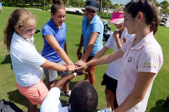 """Lincoln Park Academy girls golf team members Abby Smith (clockwise from left), Rheanna Vaughan, Angelica Holman, Samantha Lind, Cindy Montalvo and coach Raymond Williams huddle together before a team practice session at PGA Golf Club in Port St. Lucie on Wednesday, Aug. 15, 2018. This year's team is dedicating their season to two former players and coach Abigail, Tess and Mike Huber, who died in a plane crash in 2013. """"These two girls were phenoms and their story is a remarkable one,"""" Williams said to the team before Wednesday's practice. """"Our community gets to hear about the Huber sisters, that's the most important thing. This year's team gets to follow along in that legacy."""""""