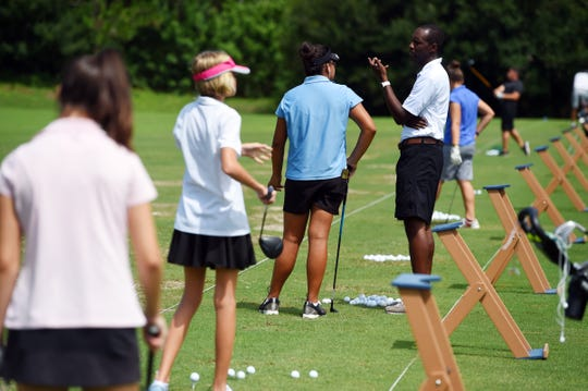 Lincoln Park Academy girls golf coach Raymond Williams talks with Angelica Holman Wednesday, Aug. 15, 2018 as the team practices on the driving range at PGA Golf Club in Port St. Lucie. The team has decided to dedicate this season to two former players, Abigail and Tess Huber, and their father and coach Michael Huber, who died in a plane crash in 2013.
