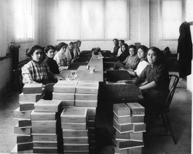 The image shows female workers putting cigars into boxes at the Kohlberg Brothers Tobacco Co., later La Internacional Cigar Factory.