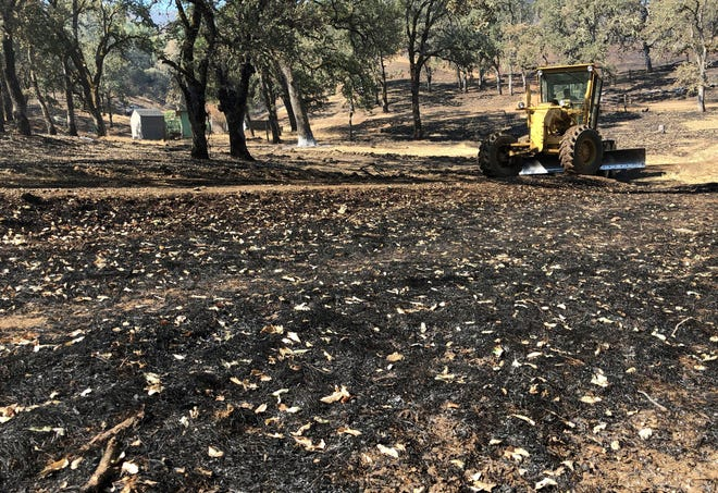 In this Aug. 10 photo, Jack Hattendorf steers a road grader to repair a dirt path near Lakeport. Hattendorf and others are working to repair the damage wrought not by flames but by firefighters trying to stop them.