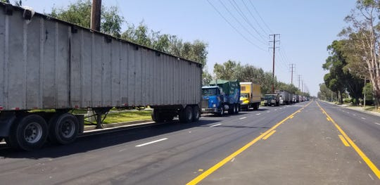 A line of trucks waits to enter the Del Norte Recycling Center in Oxnard Thursday after an acid spill was reported.