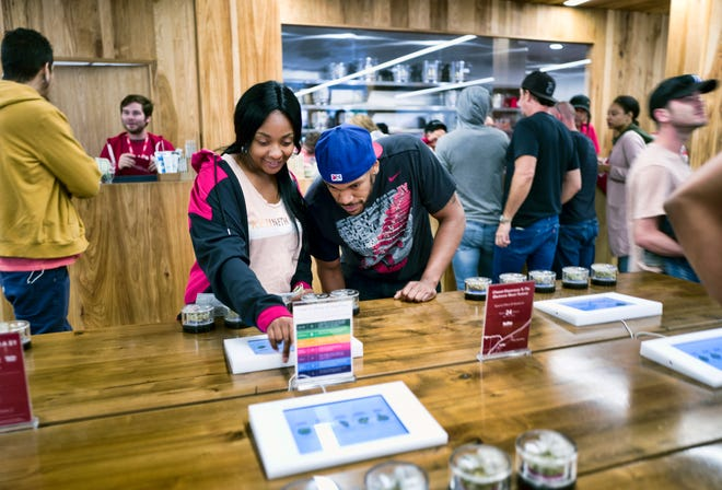 In this May 19 photo, tourists Randy Wilkie and Keya Cole from Buffalo, N.Y., check out the offerings of cannabis at one of the MedMen cannabis dispensaries in Los Angeles, prior to boarding the Green Line Trips bus tour. When it comes to the taxman, California's legal pot market is getting a sluggish start.
