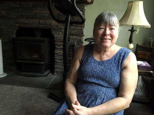 In this Aug. 9 photo, Dawn Bodley sits in her home near Lakeport. Fire swept through Bodley's property, but firefighters saved her home.