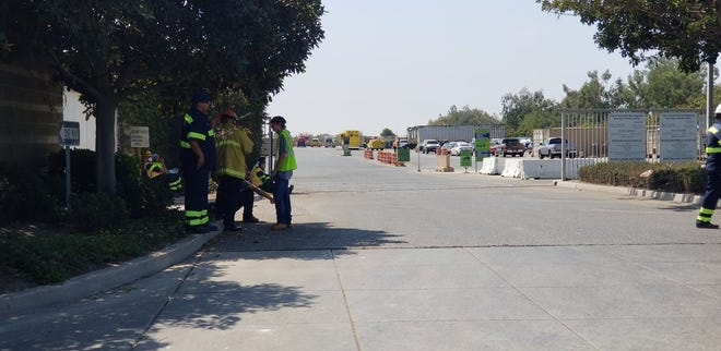 Fire crews responding to the hazardous materials spill Thursday morning at the Del Norte Recyling Center in Oxnard talk to workers.