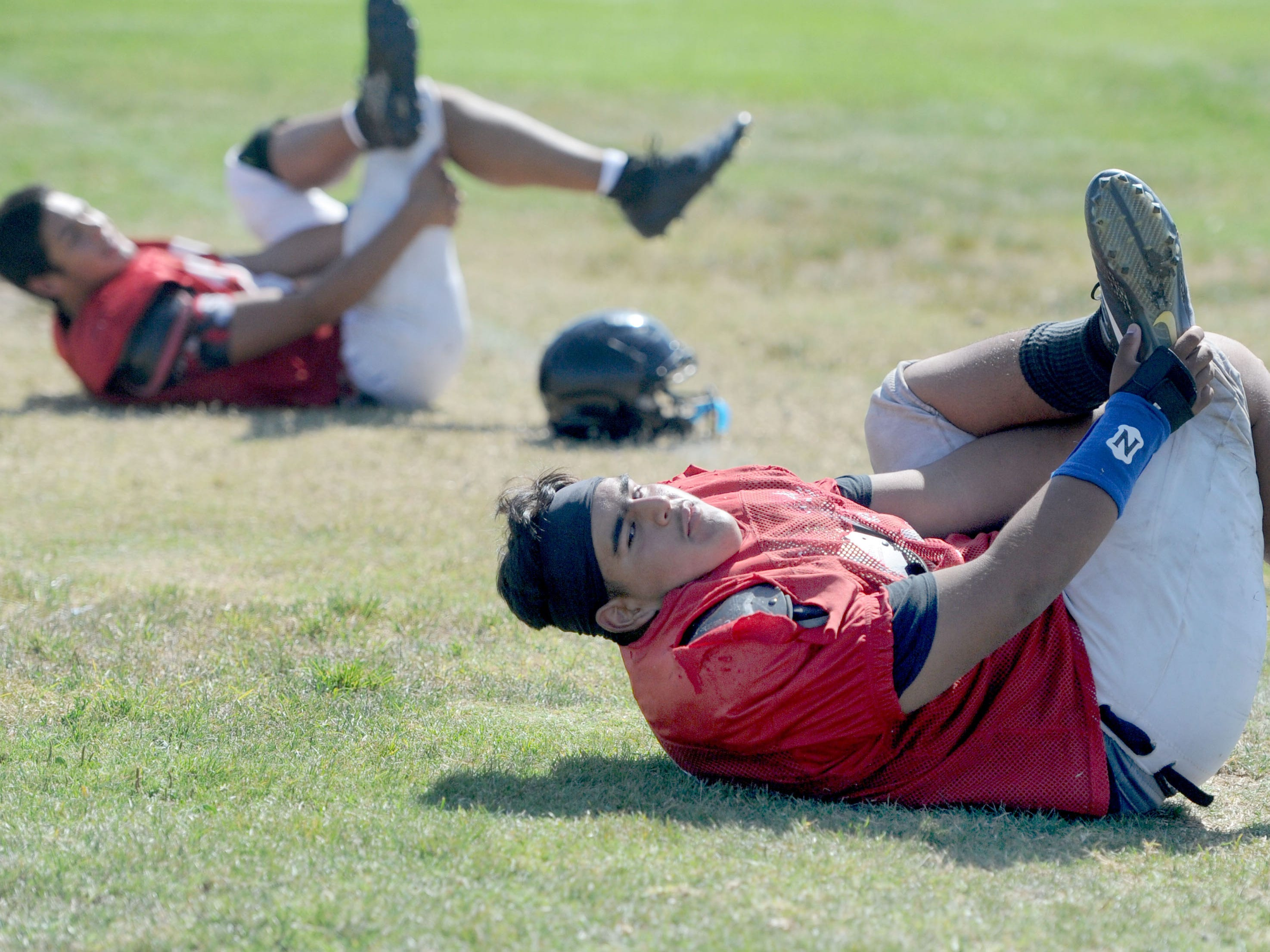 Rio Mesa High offensive linemen Steven Sanchez and teammates do some stretching during Wednesday's practice. Sanchez is the Spartans' only returning starter on the offensive line.