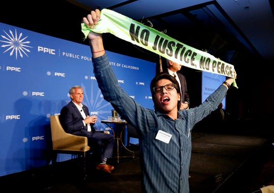 Rep. Kevin McCarthy, R-Calif., listens as protester Basilio Hernandez and other immigrant activists interrupt his appearance with the Public Policy Institute of California on Wednesday in Sacramento.