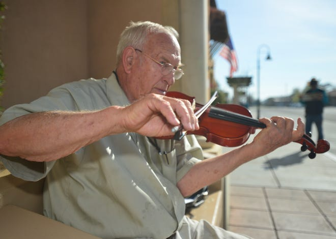 Lynn McLean, 81, of Visalia, plays the violin in front of Family Health Care Network on Oak Street.