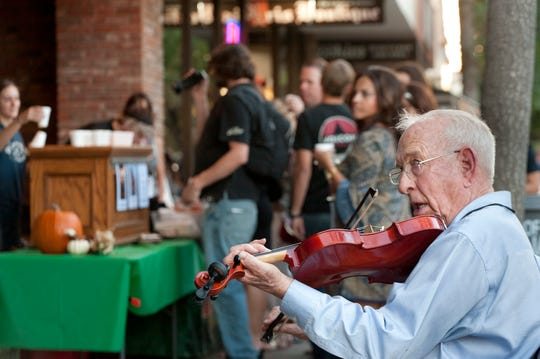 Lynn McLean plays violin on Main Street near Brewbaker's during Taste of Downtown Visalia in October 2014.