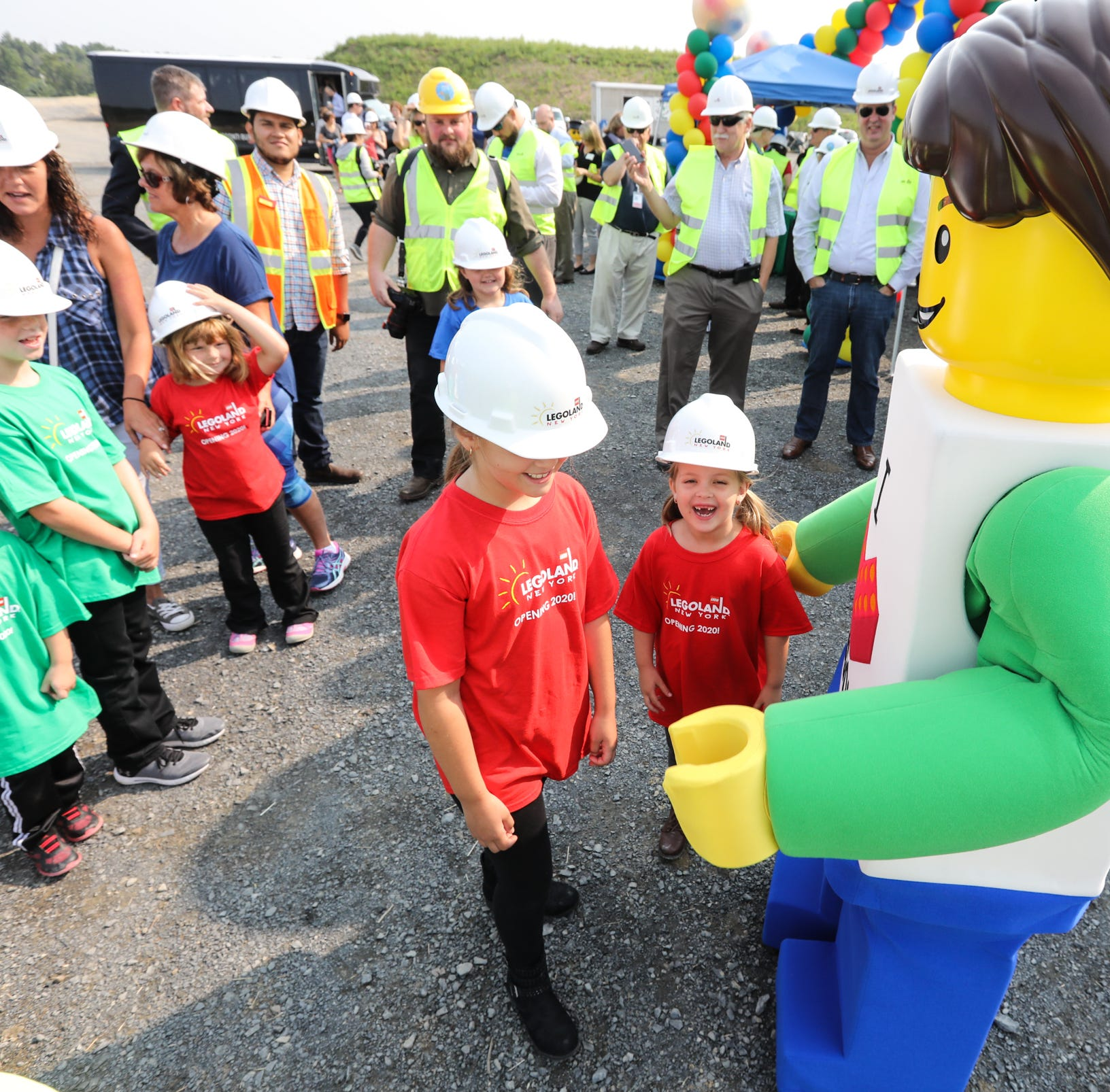 Local children take photos with a LEGO character during a tour of the construction progress of LEGOLAND New York in Goshen on Thursday, August 16, 2018.