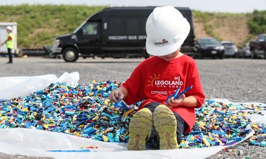 A young boy plays in a pile of LEGO pieces during a tour of the construction progress of LEGOLAND New York in Goshen on Thursday, August 16, 2018.