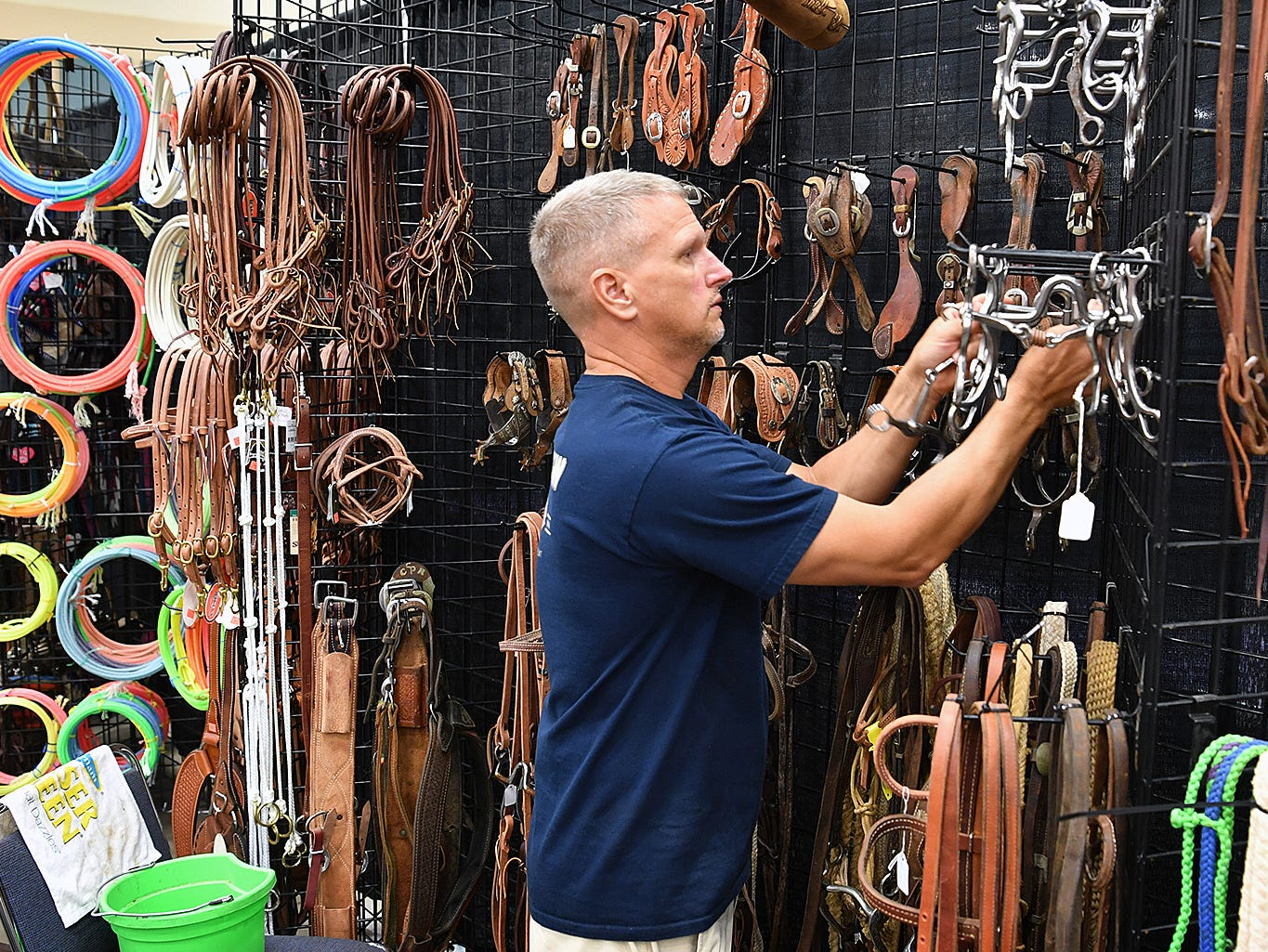 Casey Cooper of Teskey's Circle T Saddlery sets up a display of bits for the Texas Ranch Roundup Thursday morning at the Ray Clymer Exhibit Hall.