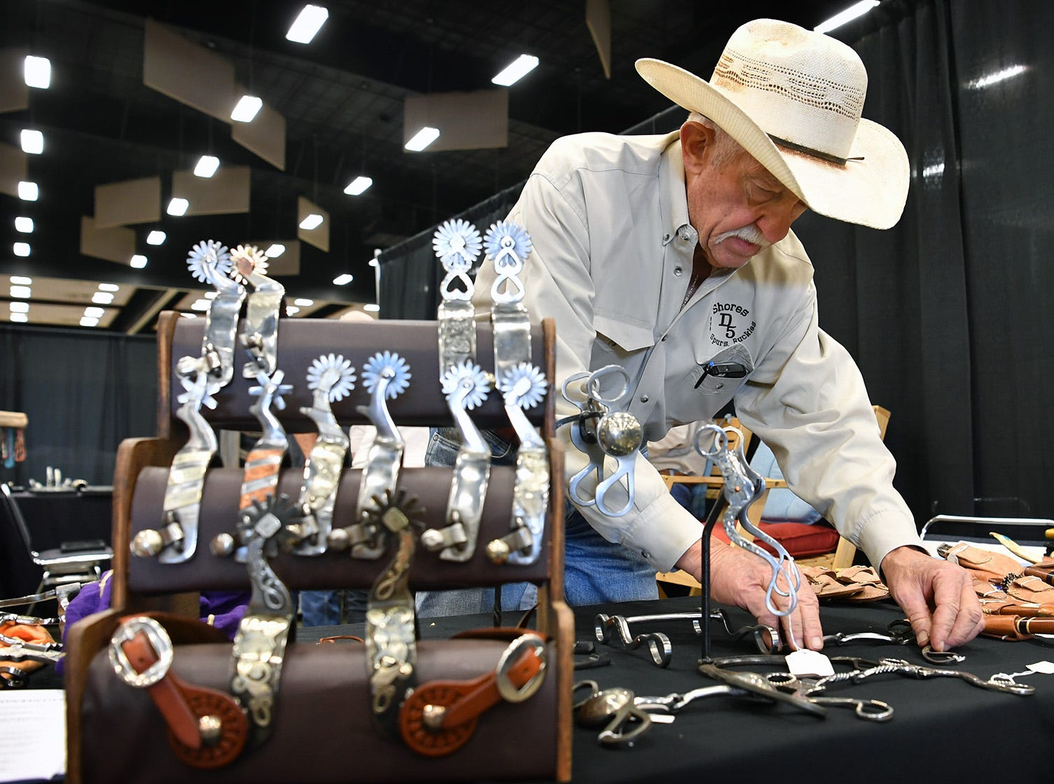 Dan Shores of D5 Metal Art lays out an arrangement of silver overlay bits and spurs for the Texas Ranch Roundup trade show Thursday morning at the Ray C;ymer Exhibit Hall.