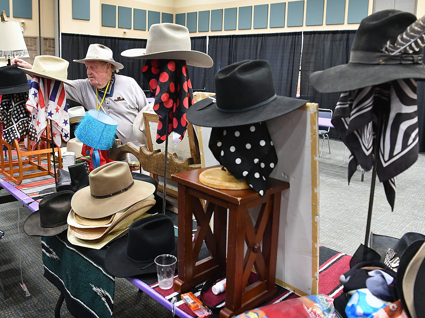 John Holden of Big Hat arranges his collection of cowboy hats and other Western items at the Texas Ranch Roundup trade show Thursday morning at the Ray C;ymer Exhibit Hall.