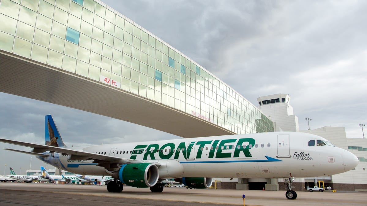 A Frontier Airbus A321 passes under the famous pedestrian bridge at  Denver International Airport on May 7, 2017.